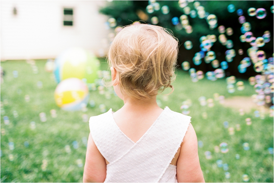 toddler playing in backyard with bubbles