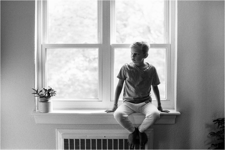 young boy sitting on window sill in charlottesville, va at home