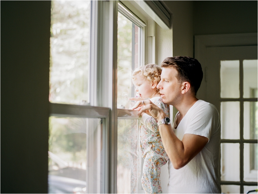 father and daughter looking out the window in charlottesville, va
